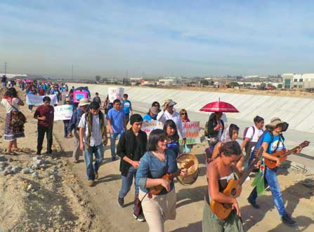 People marching along canal in Tijuana